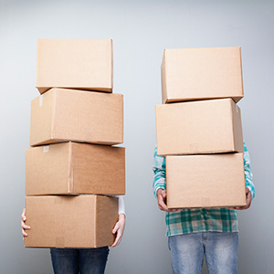 people holding stack of cardboard boxes