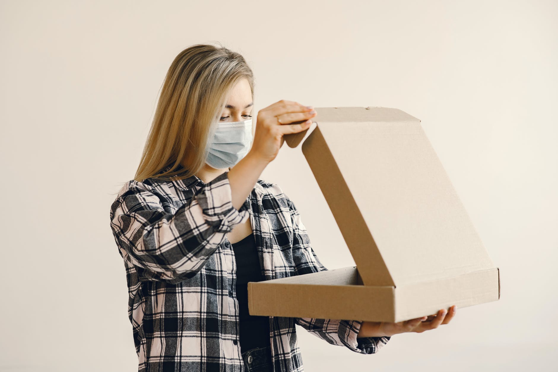 Woman with long blonde hair wearing a mask and holding an open cardboard box.